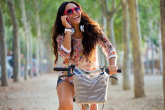 Pretty young girl riding bike and talking on the phone. Royalty Free Stock Image