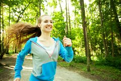 Pretty young girl runner in the forest. Stock Photos