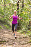 Pretty young girl runner in the forest. Stock Photo
