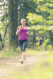 Pretty young girl runner in the forest. Royalty Free Stock Image