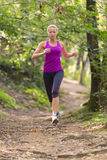 Pretty young girl runner in the forest. Stock Images
