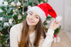 Pretty young girl in santa claus hat sit and smile near the christmas tree, in red socks. Bokeh background. Stock Photos