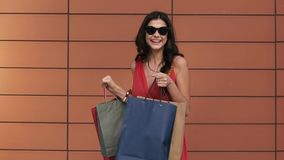 Pretty young girl showing her colorful shopping bags stock video