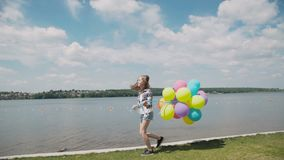 Pretty young girl shows happy emotions with balloons in hand at coustline stock video