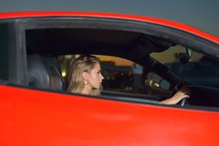 Pretty young girl sits behind the wheel royalty free stock photo