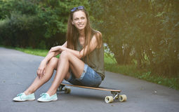 Pretty young girl sits on longboard Stock Photos