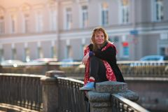 Pretty young girl sits on the railing of the canal embankment in St. Petersburg. royalty free stock photography