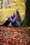Pretty young girl sitting on dried leaves in a forest. In Autumn Royalty Free Stock Photography