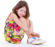 Pretty young girl sitting hugging her knees. Stock Photography