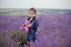Pretty young girl sitting in lavender field in nice hat boater with purple flower on it. Royalty Free Stock Photography