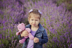 Pretty young girl sitting in lavender field in nice hat boater with purple flower on it. Royalty Free Stock Photos