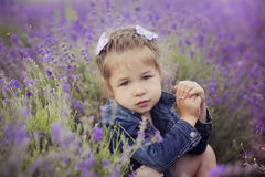 Pretty young girl sitting in lavender field in nice hat boater with purple flower on it. Stock Photo