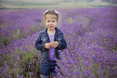 Pretty young girl sitting in lavender field in nice hat boater with purple flower on it. Royalty Free Stock Image