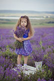 Pretty young girl sitting in lavender field in nice hat boater with purple flower on it. royalty free stock images