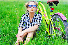 Pretty young girl sitting next to bike in grass Royalty Free Stock Photography