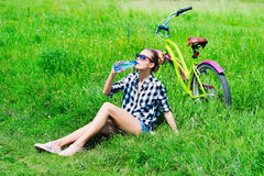 Pretty young girl sitting next to bike Royalty Free Stock Image