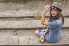A pretty young girl sitting on the steps in the city Park. Walk. Stock Photos