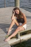 A pretty young girl sitting on a wooden boat dock royalty free stock photos