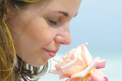 Pretty young girl smelling scent of flower. Close up portrait of beautiful young girl in love smelling the scent of a rose, isolated with blurred background stock photos