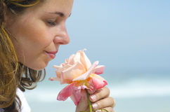 Pretty young girl smelling scent of flower. Close up portrait of beautiful young girl in love smelling the scent of a rose, isolated with blurred background stock image