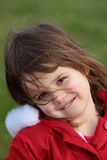 Pretty Young Girl Smiles Happily for Camera. Beautiful young toddler in a red coat poses for and smiles at the camera Stock Photo