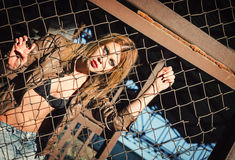 Pretty young girl standing behind metallic fence Royalty Free Stock Photo