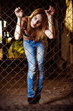 Pretty young girl standing behind metallic fence Stock Image
