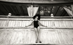 Pretty young girl standing near wooden wall in black swimwear Royalty Free Stock Images