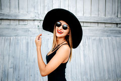 Pretty young girl standing near wooden wall in black swimwear Stock Photos
