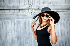 Pretty young girl standing near wooden wall in black swimwear Stock Image