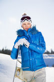 Pretty young girl standing with snowboard in her hand. Sunny winter day Royalty Free Stock Photography