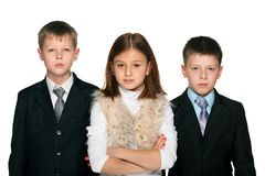 Pretty girl and two serious yong boys. Pretty young girl is standing with two serious yong boys; on the white background royalty free stock photos