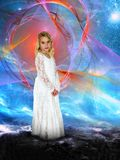 Spiritual Rebirth, Peace, Love, Hope, Nature. A pretty young girl stands in a surreal fantasy landscape. Night sky background with a nebula like cosmos is in the Royalty Free Stock Photo