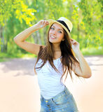 Pretty young girl in summer hat having fun outdoors. In warm sunny day Stock Image