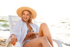 Pretty young girl in summer hat resting. At the beach Stock Photography