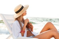 Pretty young girl in summer hat resting at the beach. Drinking cocktail, looking away Royalty Free Stock Photo