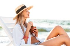 Pretty young girl in summer hat resting at the beach Royalty Free Stock Images