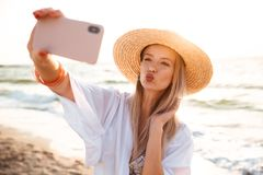 Pretty young girl in summer hat and swimwear. Spending time at the beach, taking a selfie with outsretched hand Stock Photos