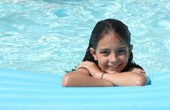 Pretty young girl in a swimming pool. On an inflatable mattress Stock Image