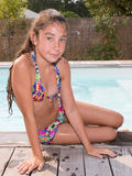 Pretty young girl in swimwear relaxing by swimming pool Stock Image