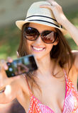 Pretty young girl taking selfies with her smart phone. Royalty Free Stock Photography