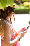 Pretty young girl texting on mobile phone in the garden. Stock Photography