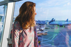Pretty young girl traveler with a backpack next to the panoramic windows of the passenger terminal  international Royalty Free Stock Image