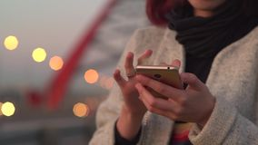 Pretty young girl using smart phone mobile in the city at night stock footage