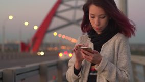 Pretty young girl using smart phone mobile in the city at night stock video