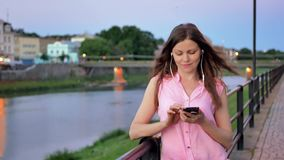 Pretty young girl using smartphone with earphones near the railing on waterfront in evening time, old city, river and stock video footage