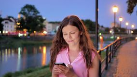 Pretty young girl using smartphone near the railing on waterfront in evening time, old city, river and bridge in the stock video footage