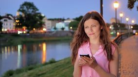 Pretty young girl using smartphone near the railing on waterfront in evening time, old city, river and bridge in the stock video