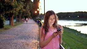 Pretty young girl using smartphone near the railing on waterfront in evening time, old city, river and bridge in the stock footage