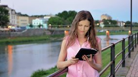 Pretty young girl using tablet computer with earphones near the railing on waterfront in evening time, old city, river. And bridge in the background stock video footage